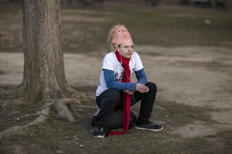 Image: A protester takes a break from wearing his Donald trump mask while sitting in front of the White House.