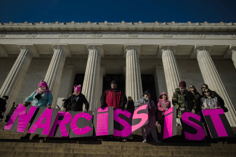 """Image: People carry placards reading \""""narcissist\"""" as they gather around Lincoln Memorial."""
