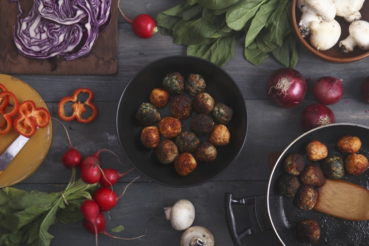 Meatballs in a pan and various vegetables on wood