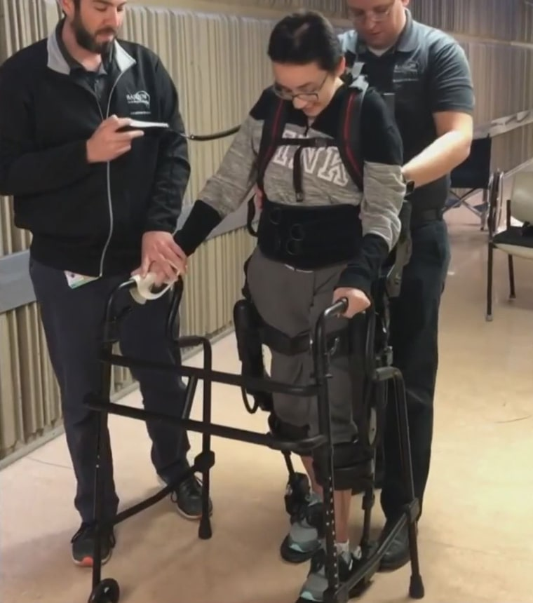 A robotic exoskeleton has helped her as she learns to walk again.