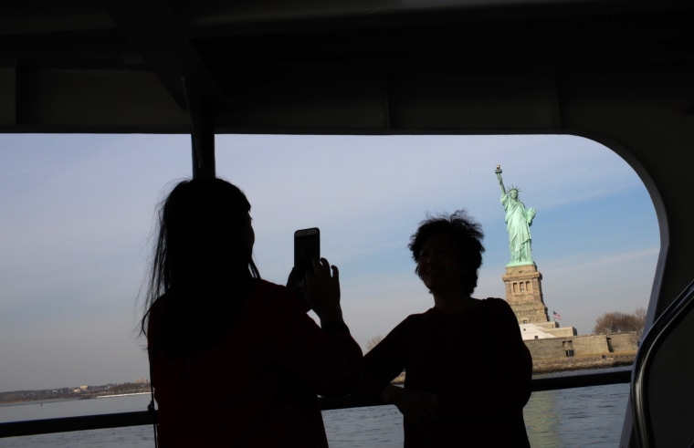 Image:  Tourists take photos of the Statue of Liberty