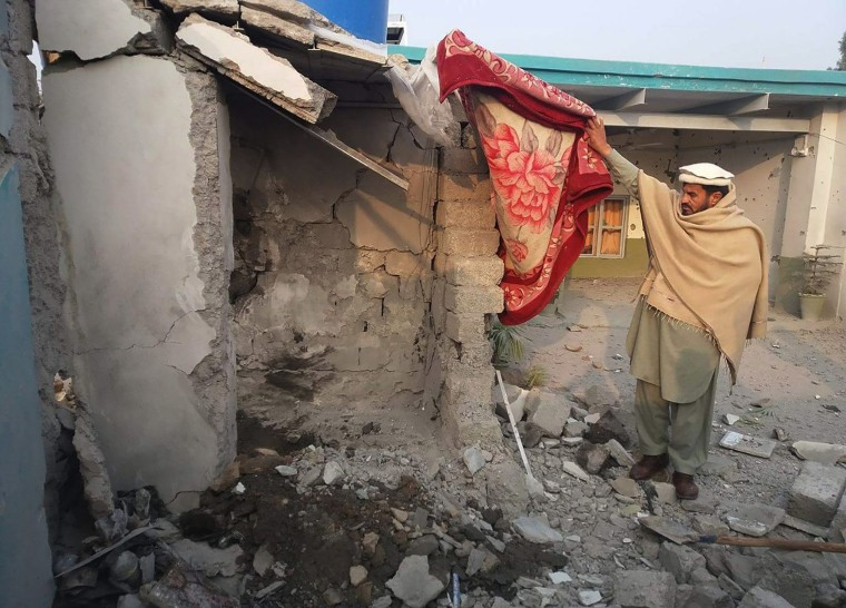 Image: A man inspects the scene of a suspected drone strike