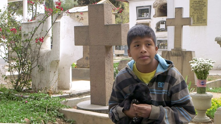 """Benjamin Obando, 11, prays and sings at a cemetery in Cochabamba, earning about $3 per day. """"I bring money home for my family, to give them food,"""" he said."""