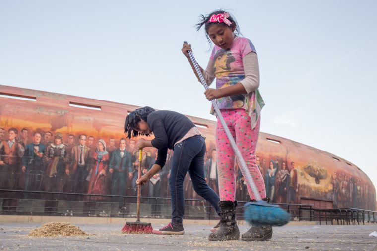 An 8-year-old child, right, and her friend sweep the pavement outside the Jaime Laredo Outdoor Theater in La Paz. Children are allowed to work for themselves or their families at age 10 in Bolivia. At 12, they can work for others.