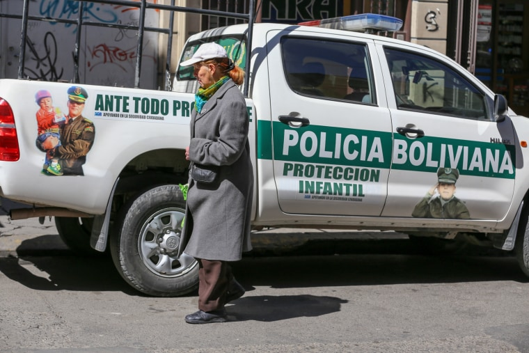 """A woman walks past a police truck marked """"child protection"""" in La Paz, where a 2014 law allows children to work as young as age 10. Government supporters say the law protects children and gives them a voice."""