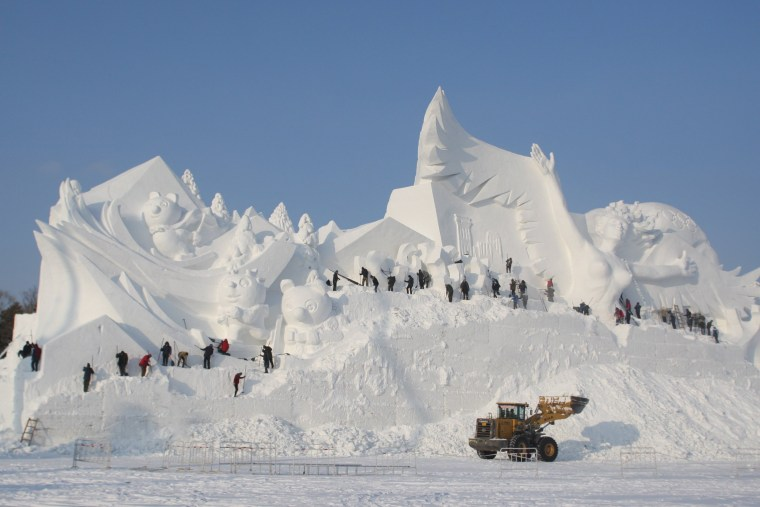 Image: People prepare a snow sculpture for the Harbin Sun Island International Snow Sculpture Art Expo in Harbin