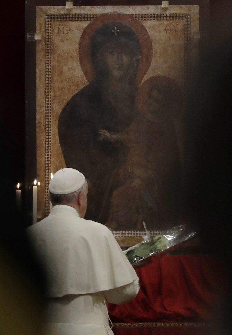 Image: Pope Francis prays in front of a portrait of the Virgin Mary