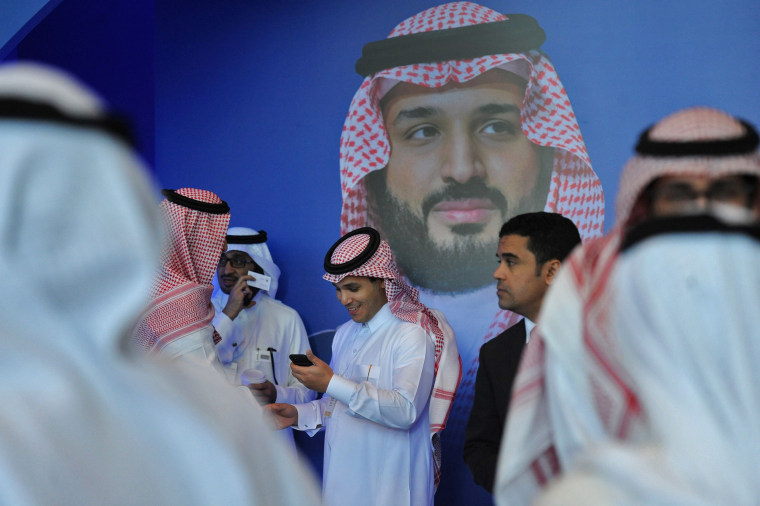 Image: Saudi men chat in front of a poster of Saudi Crown Prince Mohammed bin Salman