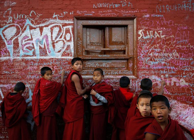 Image: Novice monks write on the wall of a Saraswati temple
