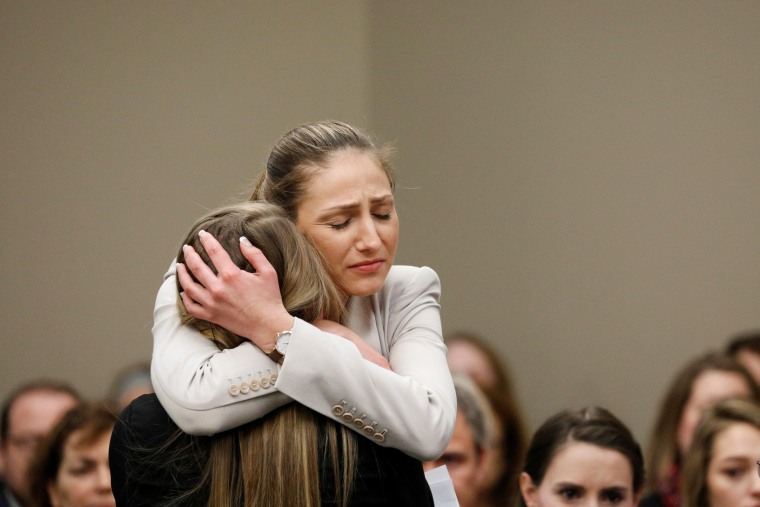 Image: Victim Emily Morales is hugged after speaking at the sentencing hearing for Larry Nassar, a former team USA Gymnastics doctor who pleaded guilty in November 2017 to sexual assault charges, in Lansing, Michigan