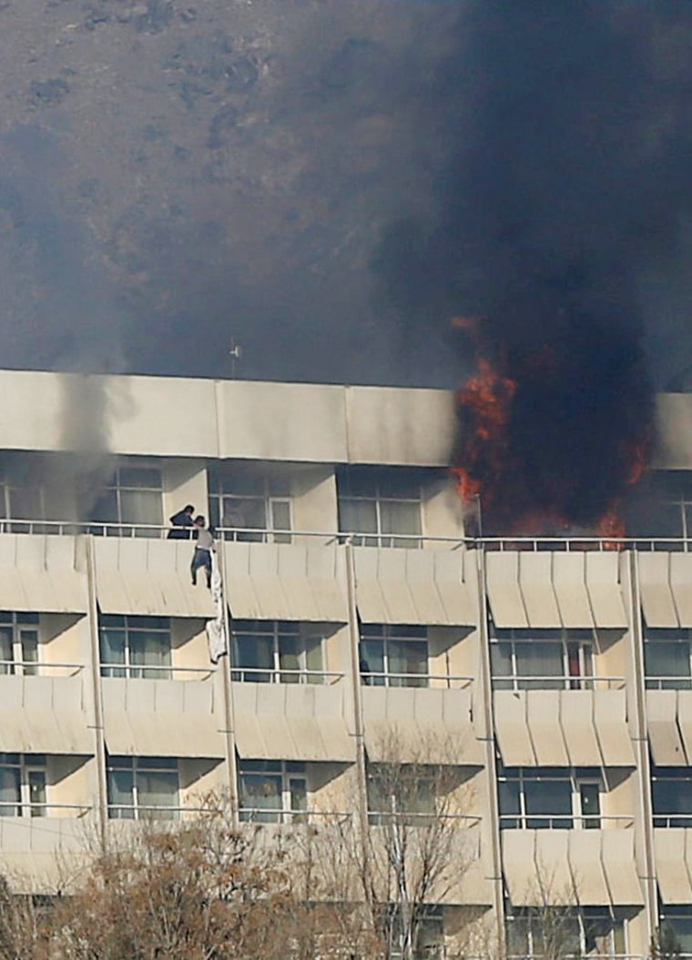 Image: A man tries to escape from a balcony at Kabul's Intercontinental Hotel during an attack by gunmen in Kabul