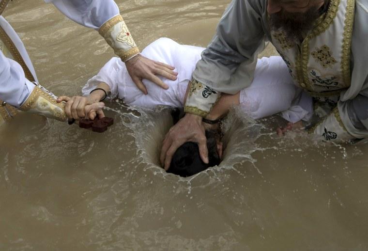 Image: Orthodox Christian pilgrims perform baptisms on Epiphany