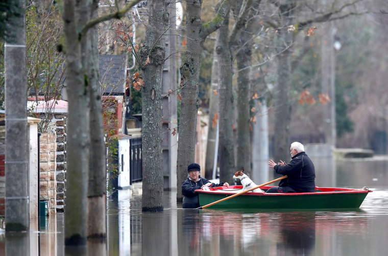 Image: Residents on a small boat leave home in a flooded street of Villeneuve-Saint-Georges