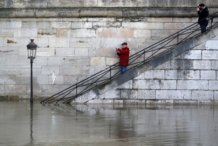 Image: Men take pictures of a street lamp on the flooded banks of the River Seine in Paris