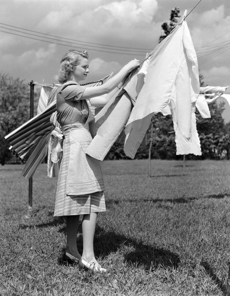 Image: A woman hangs laundry
