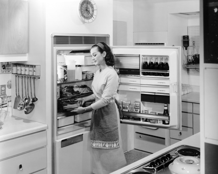Image: A woman stocks the fridge