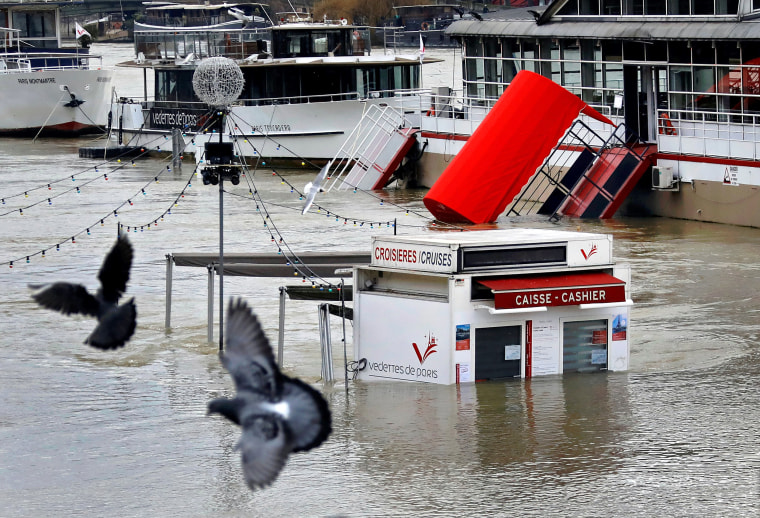 Image: A ticket booth for sightseeing boats is partly submerged by the River Seine in Paris