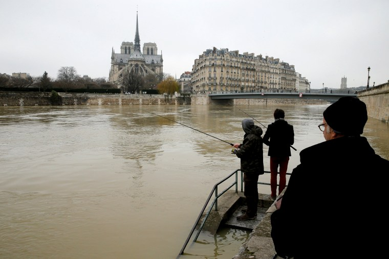 Image: Two men fish on the flooded banks of the River Seine in Paris