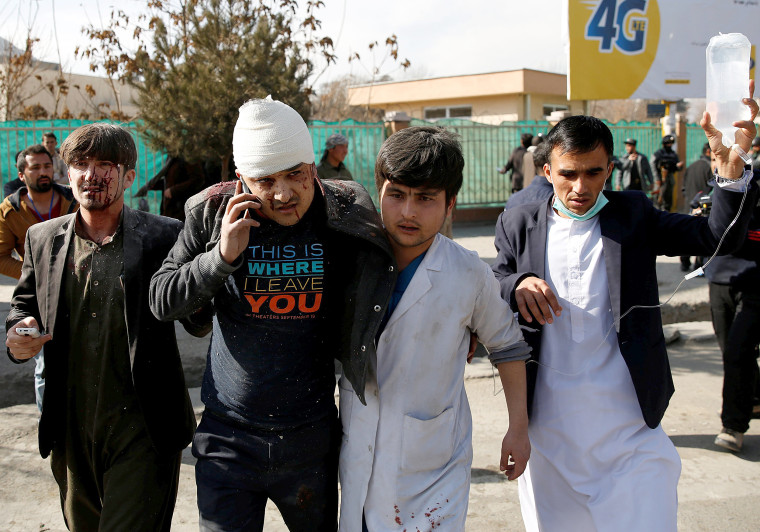 Image: People assist an injured man after a blast in Kabul