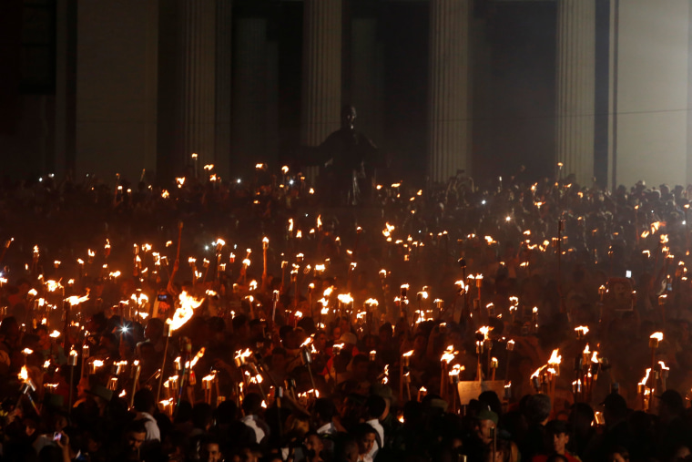 Image: Students with torches gather prior to a march in celebration of the 165th birth anniversary of Cuba's independence hero Jose Marti, in Havana