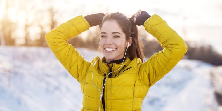 Close up portrait view of happy smiling attractive hardworking active fitness girl with earphones in winter sportswear tying a ponytail outside in snow nature.; Shutterstock ID 788947246; Purchase Order: -