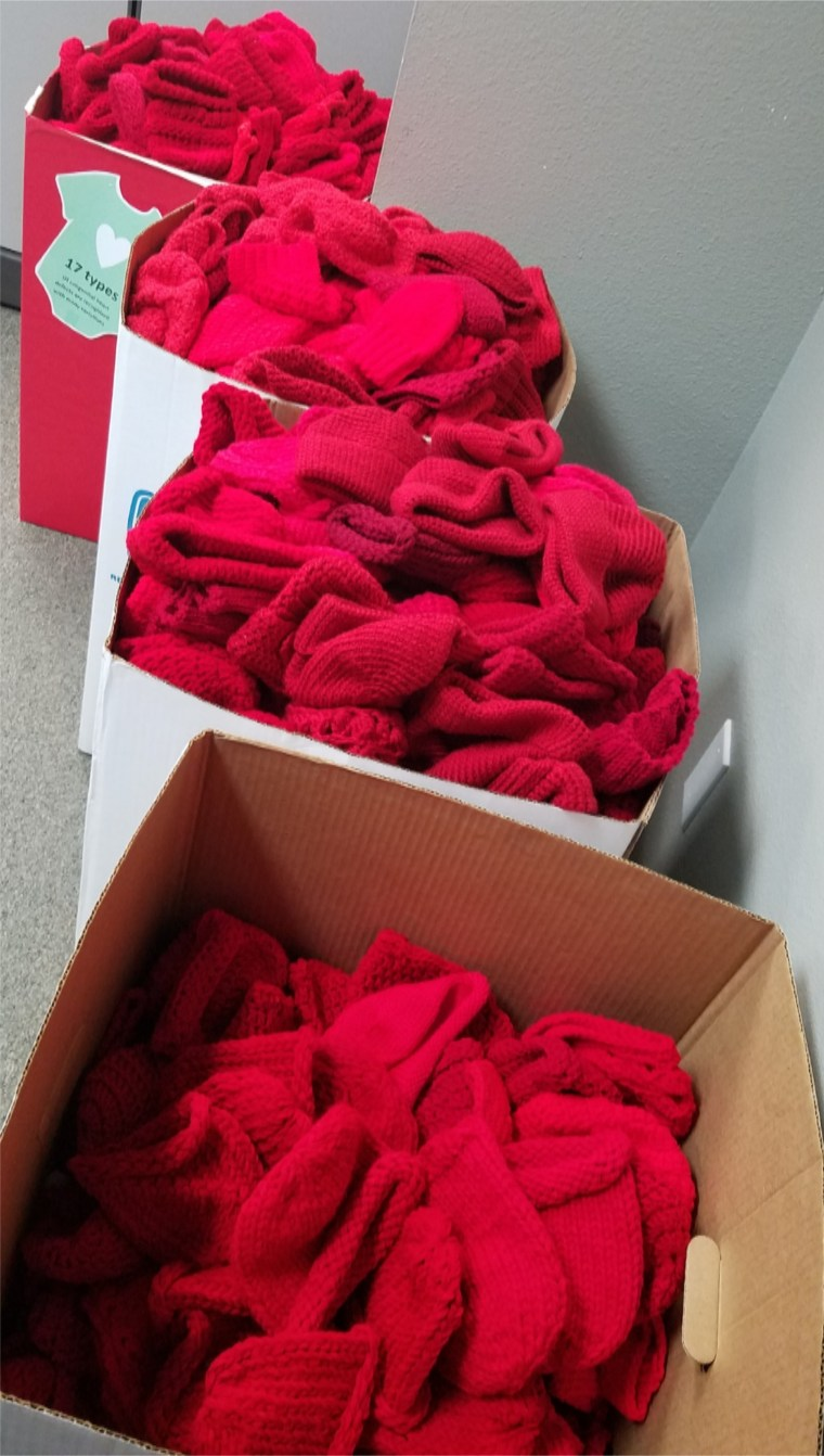 boxes of red caps knitted for babies by volunteers