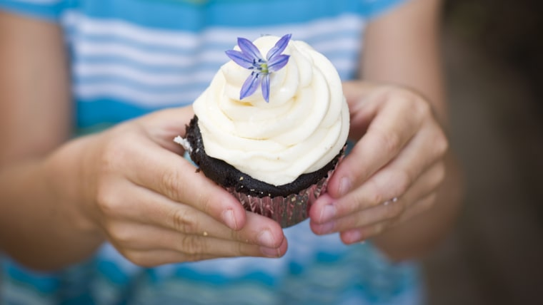 girl poses with cupcake