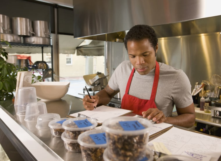 Image: A cook does paperwork in a commercial kitchen