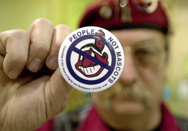 Image: A man holds an anti-mascot button to protest using Indians as mascots for sports teams