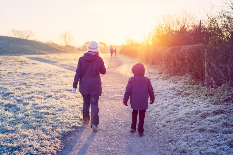 Image: Mother and son walking through a park in winter