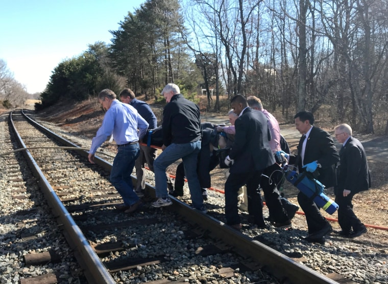 Image: One of the injured is carried across train tracks to an ambulance after a train carrying members of Congress collided with a garbage truck in Crozet, Virginia
