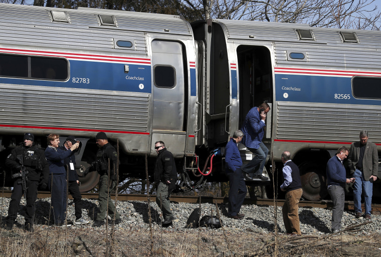 Image: Passengers watch as emergency personnel operate work at the scene of a train crash