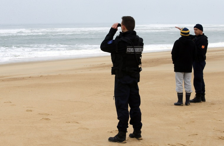 Image: French police search the coastline for clues in the disappearance of Quiksilver surfwear CEO Pierre Agnes.