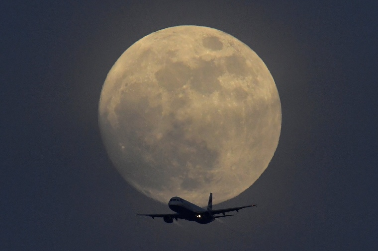 Image: A British Airways aicraft flies infront of a full moon over London