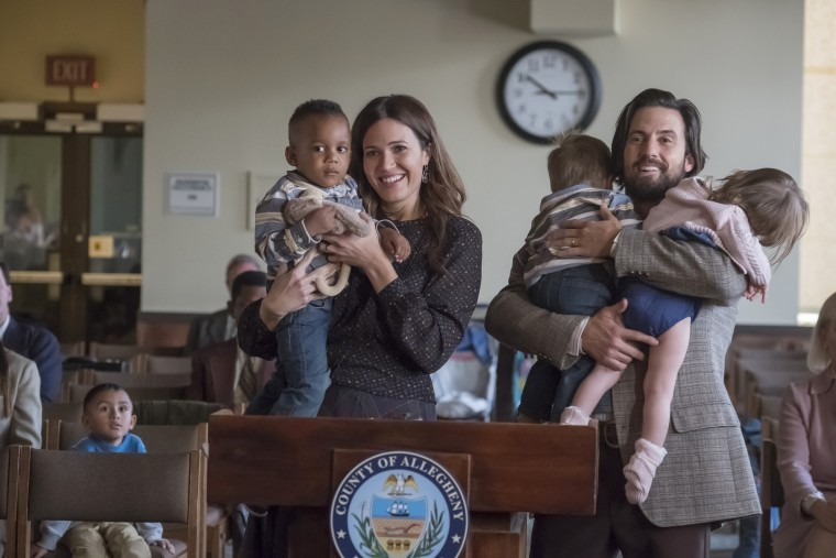 Image: Mandy Moore as Rebecca and Milo Ventimiglia as Jack hold the children in Season 2 of This Is Us.