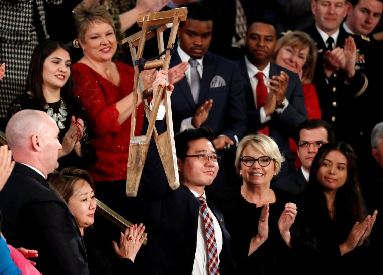 Image: North Korean defector Ji Seong-ho holds up his crutches during the State of the Union