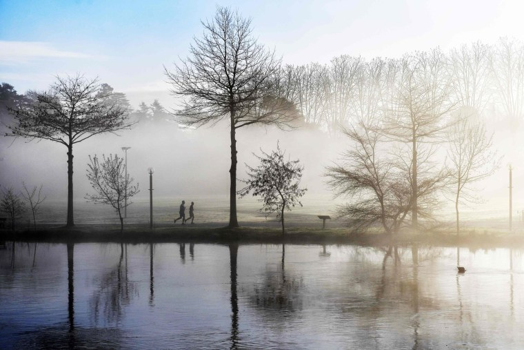 Image: Joggers run along the banks of the Sevre Nantaise river