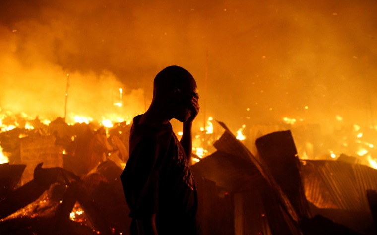 Image: A resident covers his face as he attempts to extinguish a fire that broke out at the Kijiji slums in Nairobi