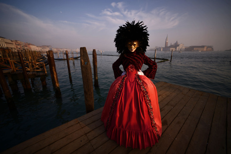Image: A masked reveler wearing a traditional carnival costume in Venice