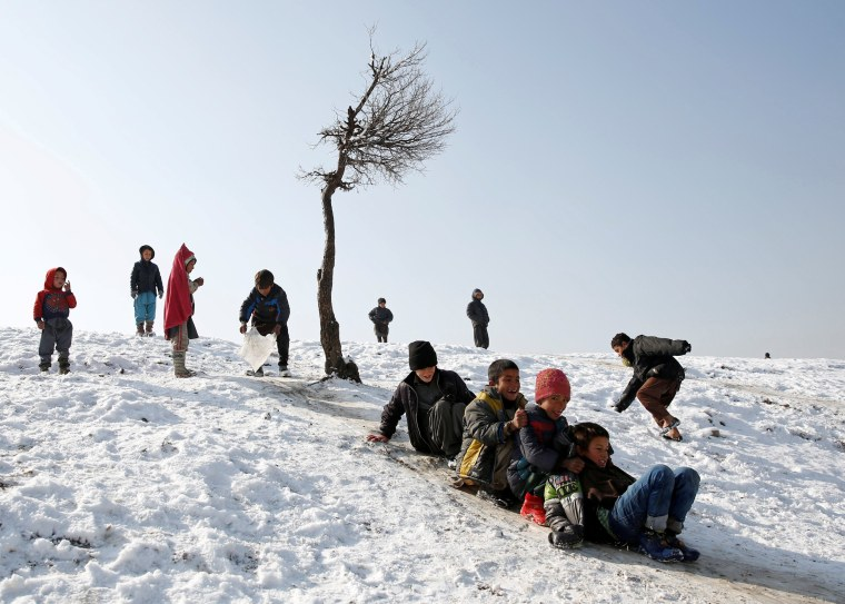 Image: Afghan boys slide down a snow-covered slope in Kabul, Afghanistan