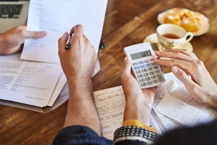 Image: Couple doing paperwork with a calculator at home