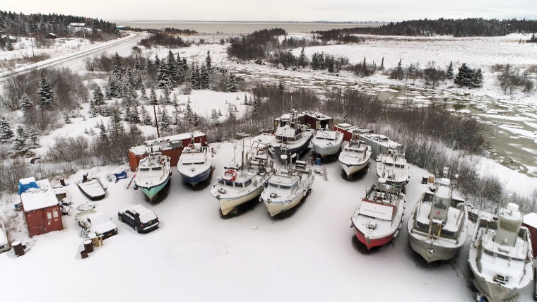 Image: Fishing boats sit idle in Dillingham, Alaska as snow falls in January.