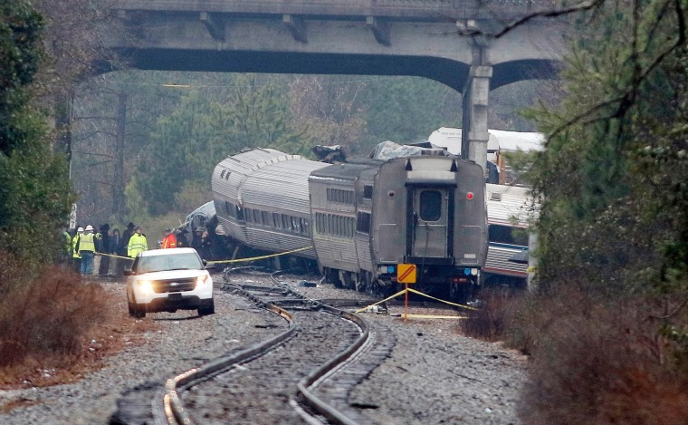 Image: Investigators make their way around the train wreckage under the Charleston Highway overpass where two trains collided
