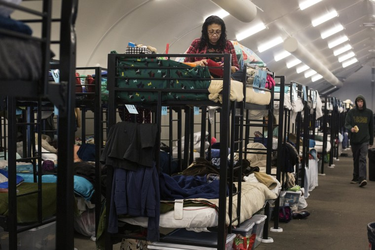 Image: Silvia Saliman sits on her bunk bed in a temporary shelter for the homeless run by the Alpha Project