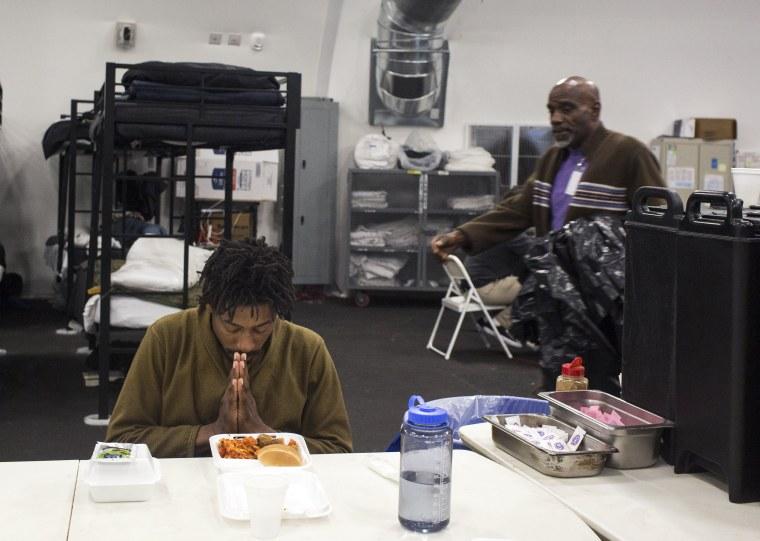Image: Resident Derek Diamond, 31, prays before eating a second helping of dinner in a temporary shelter for the homeless