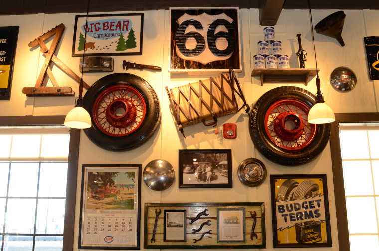 Historical decorations pay homage to California's Route 66, such as an antique tire, luggage rack and suitcase, old motor oil cans, and an antique Esso calendar from June 1969.