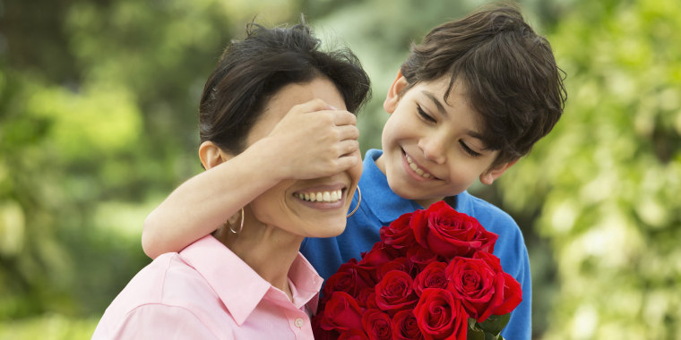 Boy giving mother bouquet of roses