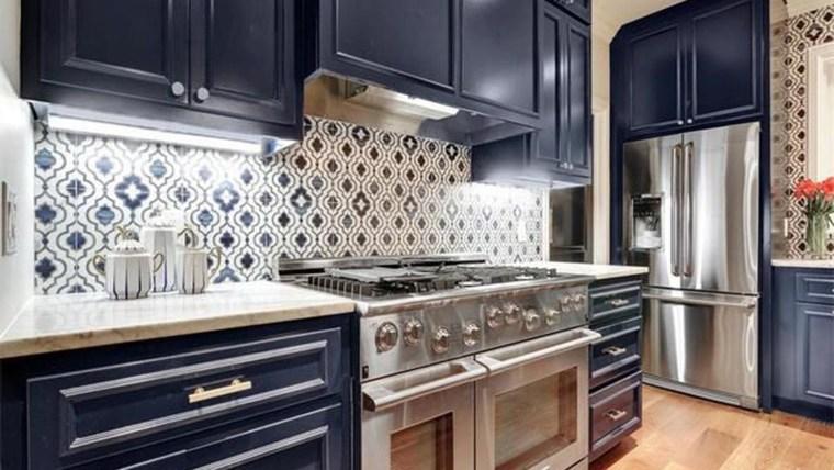 A kitchen with dark blue cabinets