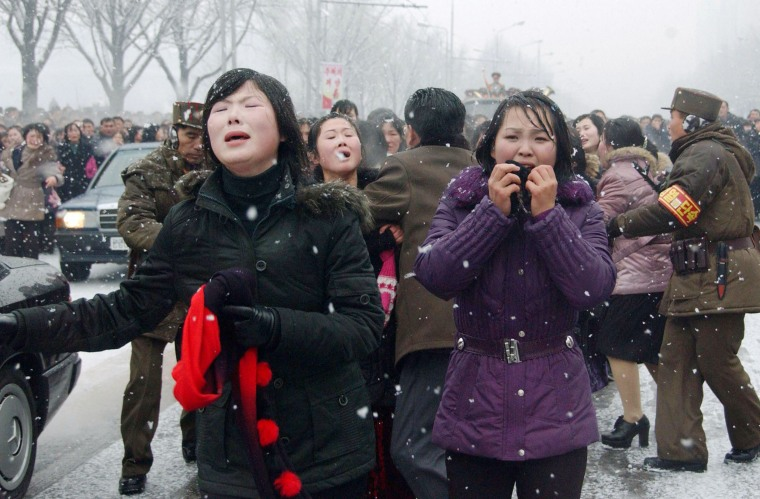 Mourners react as a car holding Kim Jong-Il's body passes by during the funeral procession in Pyongyang, North Korea on Dec. 28, 2011. Millions of grief-stricken people turned out to mourn Kim Jong-Il, whose death has left the world scrambling for details about his young successor.