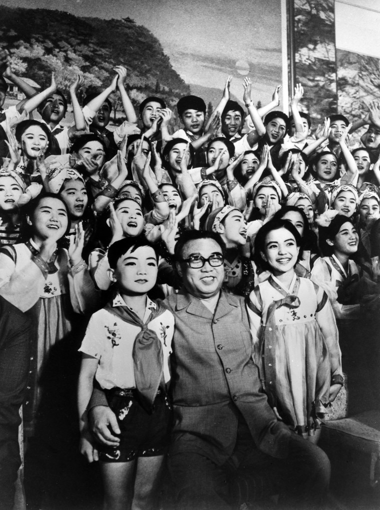 Former Prime Minister of North Korea Kim Il Sung smiles in a souvenir picture after enjoying the music and dance synthesis act by the Pyongyang student art troupe, performed in Japan on July 2, 1978.
